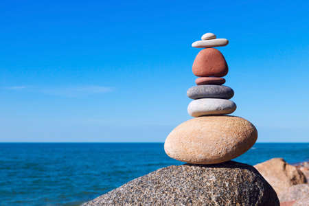 sustained: Concept of harmony and balance. Balance and poise stones against the sea. Rock zen in the form of scales