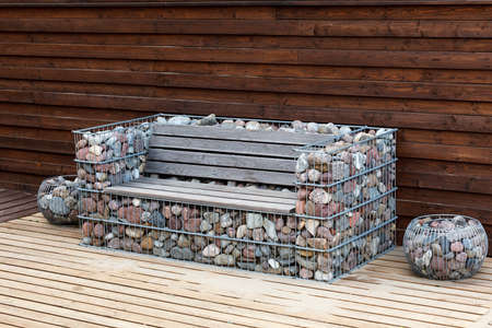 cobblestones: unusual wooden bench with a frame made of cobblestones Stock Photo