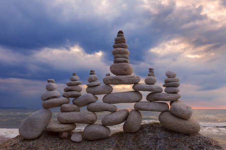 sustained: Concept of harmony and balance. Rock Zen at sunset. Balance and poise stones against the sea Stock Photo