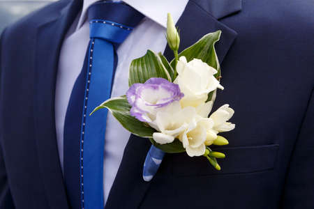 lapel: beautiful grooms boutonniere of lilies and roses Stock Photo