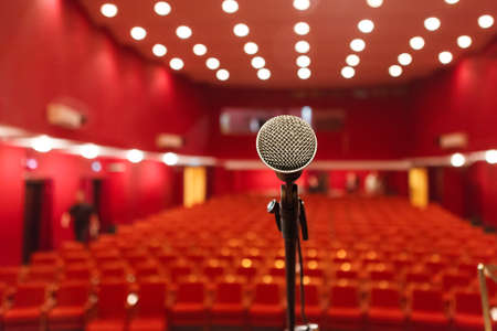 microphone on a background of red hall with seating for spectators. chairs for the audience