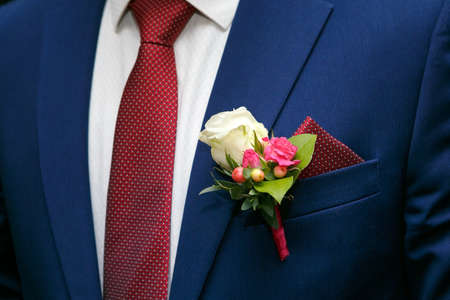 dark blue grooms suit and boutonniere of white and red roses and the handkerchief in the breast pocket