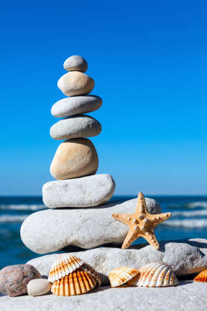 pyramid of white stones and shells on a background of blue sky and sea Stock Photo