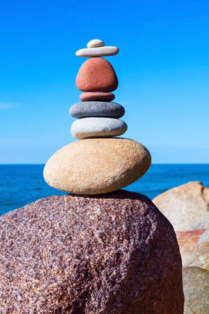 Pyramid from colored stones on a background of the sea. balance and tranquility concept