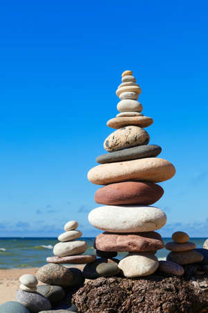 sustained: A high pyramid of stones of different colors on the background of sea and blue sky