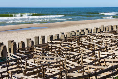 fascine cage made from boards to keep the sand on the beach. Protective structures