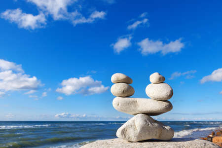 concept of balance between work and life. Balance stones against the sea. Rock zen in the form of scales