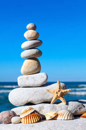 equipoise: pyramid of white stones and shells on a background of blue sky and sea Stock Photo