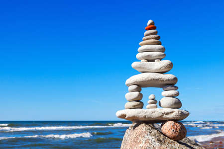 High pyramid of white stones balance on the edge of the cliff on the sea background. Concept of harmony and balance Stock Photo