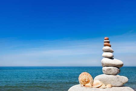 Concept van vrede en harmonie. Een piramide van witte stenen en schelpen op de achtergrond van de zomer zee. Kopieer ruimte