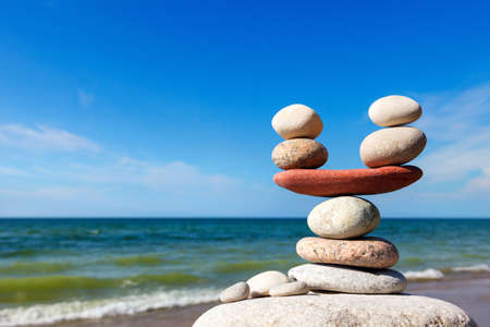 Stones balance on the background of sea and blue sky. Rock zen in the form of scales. The concept of balance