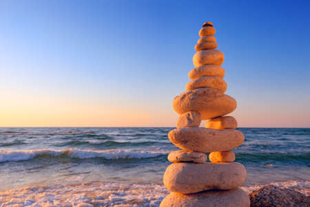 Concept of harmony and balance. Rock Zen at sunset. Balance and poise stones against the sea Banco de Imagens