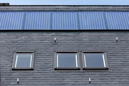 Roof of black slate tiles, roof Windows and fixed solar panels