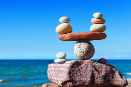 Symbolic scales of stones against the background of the sea and blue sky. Concept of harmony and balance. Pros and cons concept