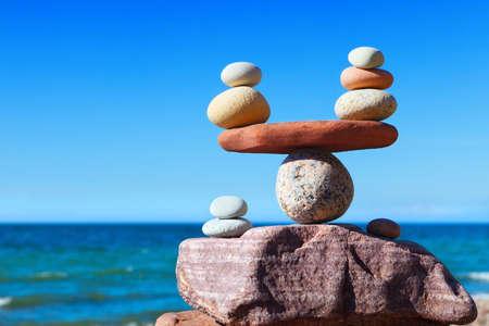 Escalas simbólicas de piedras contra el fondo del mar y el cielo azul. Concepto de armonía y equilibrio. Concepto Pros y contras