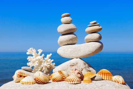 Symbolic scales of white stones, shells and coral on a background of the summer sea and blue sky. Concept of harmony and balance.