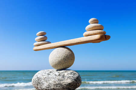 Symbolic scales of stones on the background of the sea and blue sky. Concept of harmony and balance. Pros and cons concept Standard-Bild