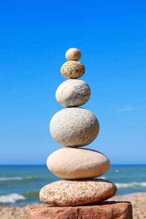 White, round stones balance on a background of blue sky and sea. Concept of balance and harmony Stock Photo