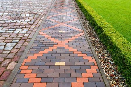 Mooie bestrating van rode en bruine keramische tegels na een regen. Voetgangerpad versierd met een bijgesneden sierstruiken en kiezelstenen Stockfoto
