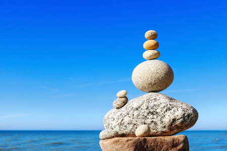 equilibrium: Rock zen pyramid of white and pink stones on a background of blue sky and sea. Concept of balance, harmony and meditation