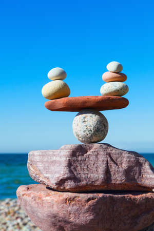 Symbolic scales of stones against the background of the sea and blue sky. Concept of harmony and balance. Pros and cons, work - life concept Stock Photo