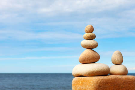 White stones balance on a background of blue sky and sea. Concept of balance and harmony. Rock zen