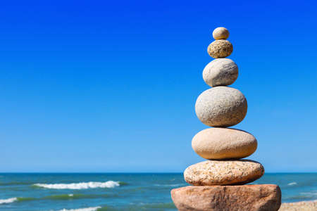 Rock zen pyramid of white and pink stones on a background of blue sky and sea. Concept of balance, harmony and meditation
