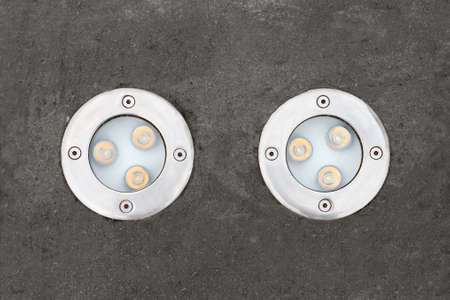 two round Vandal-proof LED lights on the sidewalk Stock Photo