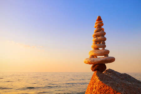 Stones balance on a background of sea sunset. Calm and meditation. Concept of harmony and balance. copy space Standard-Bild