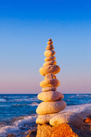 Rock zen pyramid of white stones in the pink rays of the setting sun against the sea Concept of balance, harmony and meditation Stock Photo