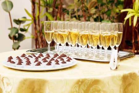 lot of glasses with champagne and chocolates on the buffet table