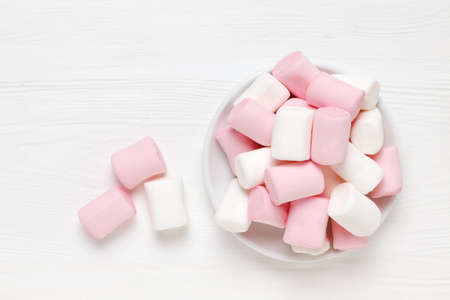 White and pink marshmallow on a saucer on a white wooden surface. pink mood.Top view Standard-Bild