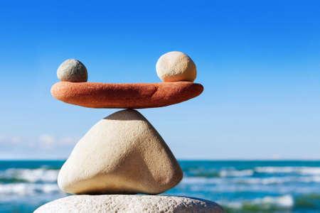 Pojęcie harmonii i równowagi. Równoważenie kamieni na tle morza. Rockowy zen w postaci łusek Zdjęcie Seryjne
