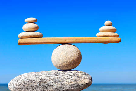Symbolic scales of stones on the background of the sea and blue sky. Concept of harmony and balance. Pros and cons concept Stock Photo