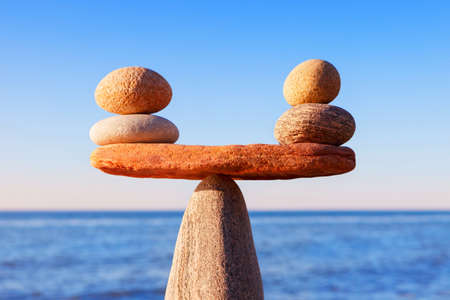 Symbolic scale of the stones on sea background closeup. Concept of harmony and balance. work-life, emotional balance Archivio Fotografico