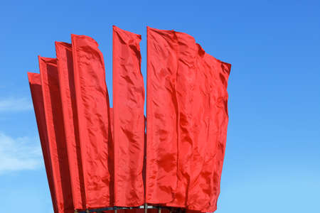 Many red flags waving in the wind against the blue sky 版權商用圖片