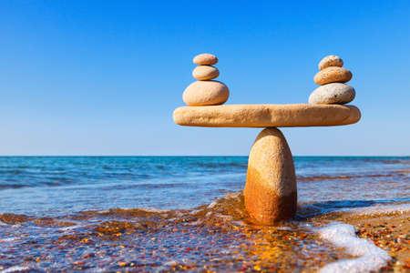 Symbolische Skala der Steine auf Seehintergrundnahaufnahme. Konzept der Harmonie und des Gleichgewichts. Work-Life, emotionale Balance