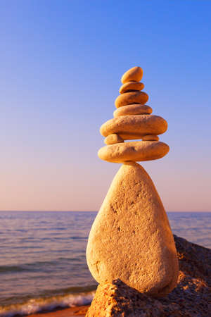 Stones balance on a background of sea sunset. Calm and meditation. Concept of harmony and balance. Imagens