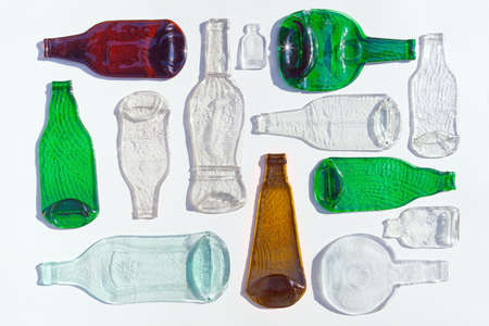 Composition of molten, flat bottles of different colors on white background. Flat lay, top view