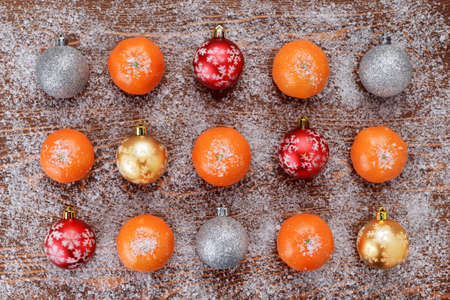 Pattern of Christmas toys and tangerines on a Board covered with frost. Christmas and new year concept. Flat lay, top view