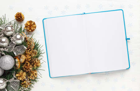 Christmas wreath and Blank open notepad on white background. New year goals concept, mockup, top view, copy space