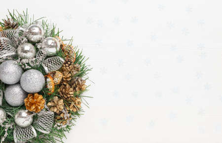 Christmas wreath of cones, silver balls and fir branches on white background. New year decorations, top view, copy space