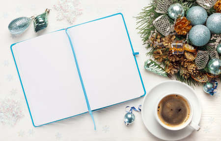 Christmas wreath, cup of coffee and Blank open notepad on white background. New year goals concept, mockup, top view, copy space Stock Photo