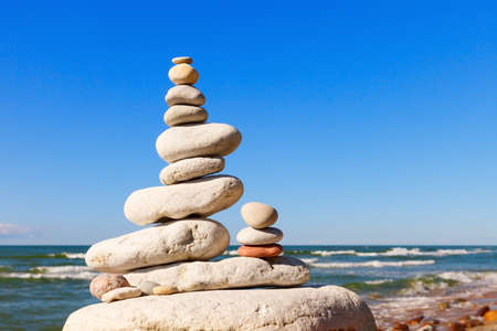 High pyramid of white stones balance on the edge of the cliff on the sea background. Concept of harmony and balance Stockfoto