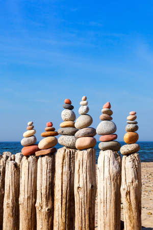 Several of the Rock zen pyramid of white and pink pebbles standing on the old breakwater on the beach. Concept of balance, harmony and meditation Stock Photo
