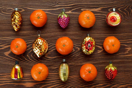 pattern of antique Christmas toys and tangerines on a dark wooden surface. Christmas and new year concept. Flat lay, top view