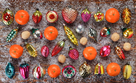 Pattern of antique Christmas toys, walnuts and tangerines on a Board covered with frost. Christmas and new year concept. Flat lay, top view