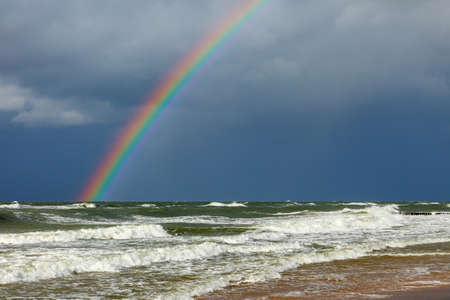 Bright rainbow on the background of storm clouds over the raging sea