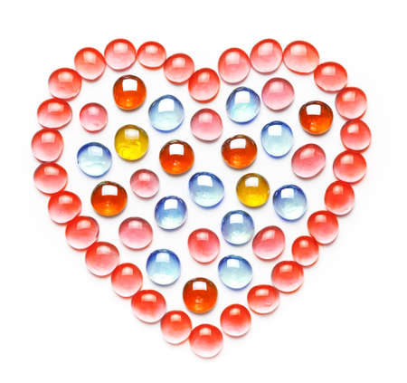 Heart made of colorful glass beads. Isolated on white background. Valentines day concept. Flat lay, top view Stockfoto