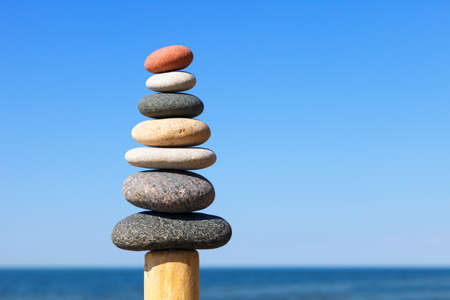 Gray and red balance pebbles on the clear blue sky background. Concept of harmony, balance and meditation.